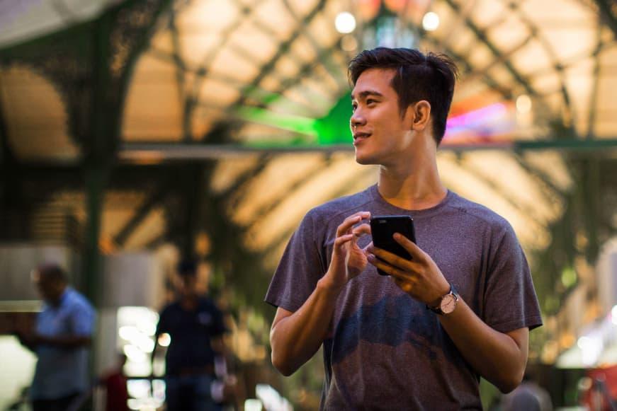 global rider young man holding phone atrium